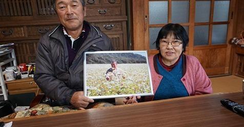 蕎麦畑での写真を持つ長谷川健一さん花子さん夫妻